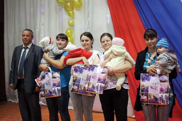 В.В. Покровский вручает памятные подарки семьям, где появились новорожденные