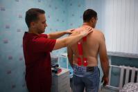 Специалист «Диамеда» А. В. Скрябин проводит аппликацию тейпами